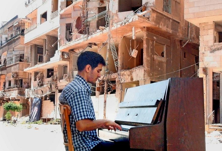 TO GO WITH AFP STORY BY Rana Moussaoui Ayham al-Ahmed, a resident of Damascus' Yarmuk Palestinian refugee camp, plays the piano in the middle of the street near destroyed buildings, on June 26, 2014. In the Yarmuk camp in southern Damascus, the notes escape a piano set in a scene of destruction and the children in Ayham al-Ahmed's little group sing of hunger and suffering. The music in the Syrian camp, under siege for a year and wracked by violence, seems at odd with the brutality that is all around. AFP PHOTO/RAMI AL-SAYED (Photo credit should read RAMI AL-SAYED/AFP/Getty Images)